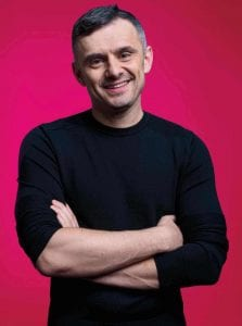 Gary Vaynerchuk with arms folded in black long sleeve in front of a red backdrop